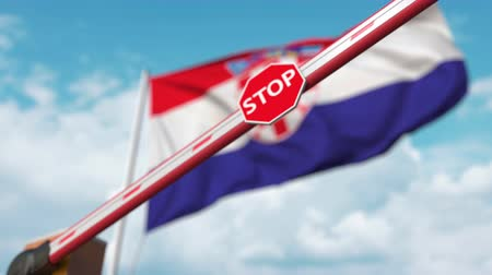 определенный : Closing boom barrier with stop sign against the Croatian flag. Restricted entry or certain ban in Croatia Стоковые видеозаписи