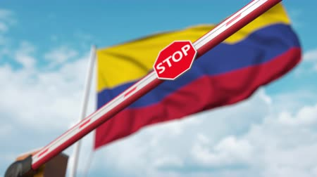 korlátozás : Closed boom gate on the Colombian flag background. Restricted entry or certain ban in Colombia