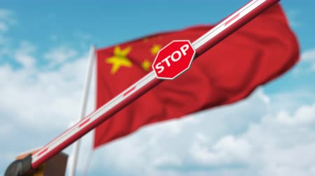 определенный : Closing boom barrier with stop sign against the Chinese flag. Restricted entry or certain ban in China