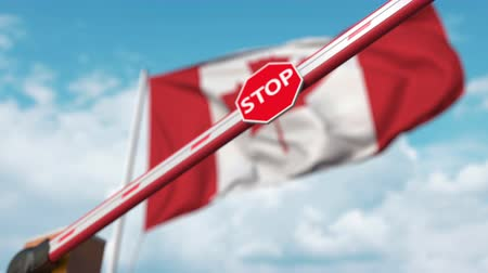 korlátozás : Closing boom barrier with stop sign against the Canadian flag. Restricted entry or certain ban in Canada