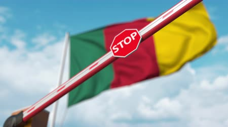 определенный : Closed boom gate on the Cameroonian flag background. Restricted entry or certain ban in Cameroon Стоковые видеозаписи