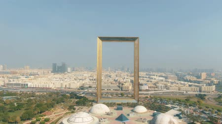 within : DUBAI, UNITED ARAB EMIRATES - DECEMBER 26, 2019. Aerial shot of golden Dubai Frame and the Zabeel Park within cityscape Stock Footage