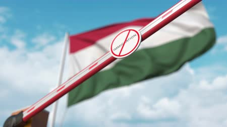 tilalom : Closed boom gate with no immigration sign on the Hungarian flag background. Border closure or immigration ban in Hungary