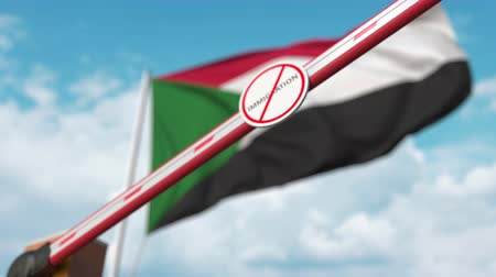 göçmen : Closed boom gate with no immigration sign on the Sudanian flag background. Restricted border crossing or immigration ban in Sudan