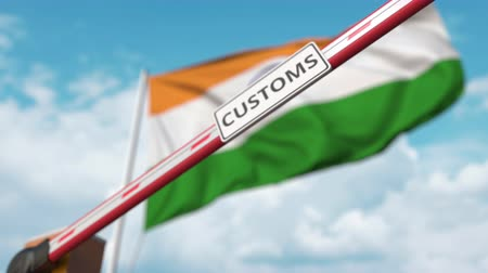 regras : Barrier gate with CUSTOMS sign being closed with flag of India as a background. Indian Border closure or protective tariffs