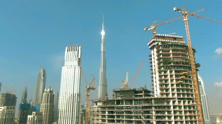 khalifa : DUBAI, UNITED ARAB EMIRATES - DECEMBER 30, 2019. Aerial shot of the Burj Khalifa tower behind skyscraper construction site Stock Footage