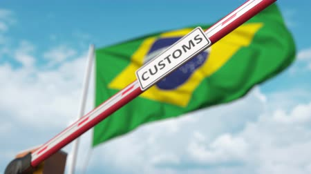 brezilya : Closed boom gate with CUSTOMS sign on the Brazilian flag background. Border closure or protective tariffs in Brazil Stok Video