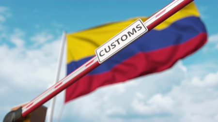 bariéra : Closed boom gate with CUSTOMS sign on the Colombian flag background. Border closure or protective tariffs in Colombia