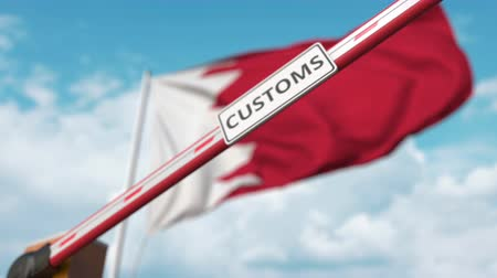prohibición : Closed boom gate with CUSTOMS sign on the Bahraini flag background. Border closure or protective tariffs in Bahrain