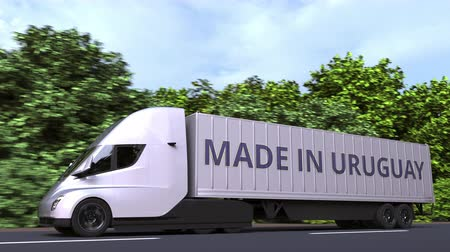 Уругвай : Modern electric semi-trailer truck with MADE IN URUGUAY text on the side. Uruguayan import or export related loopable 3D animation Стоковые видеозаписи