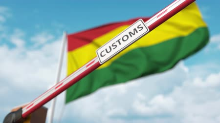kural : Closing boom barrier with CUSTOMS sign against the Bolivian flag. Border closure or protective tariffs in Bolivia Stok Video