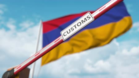 entry : Barrier gate with CUSTOMS sign being closed with flag of Armenia as a background. Armenian border closure or protective tariffs