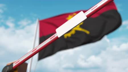 szabály : Closed boom gate with blank sign on the Angolan flag background. Border closure or protective tariffs in Angola Stock mozgókép