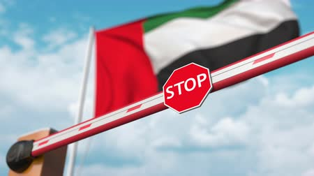 immigratie : Opening boom barrier with stop sign against the UAE flag. Free border crossing or lifting a ban