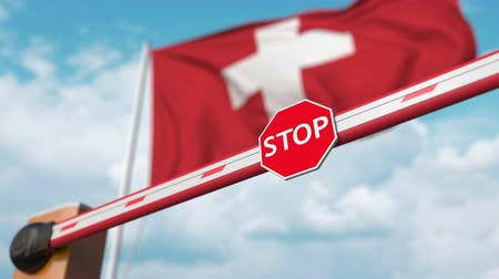 authorise : Opening boom barrier with stop sign against the Swiss flag. Free border crossing or lifting a ban in Switzerland