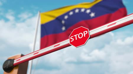 gümrük : Opening boom barrier with stop sign against the Venezuelan flag. Free entry or lifting a ban in Venezuela Stok Video