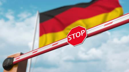 invite : Opening boom barrier with stop sign against the German flag. Free entry or lifting a ban in Germany
