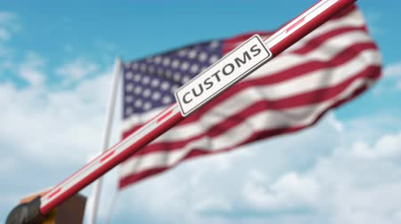 kural : Closing boom barrier with CUSTOMS sign against the American flag. Border closure or protective tariffs in the USA Stok Video