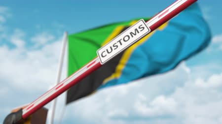 border crossing : Closing boom barrier with CUSTOMS sign against the Tanzanian flag. Restricted border crossing or protective tariffs in Tanzania