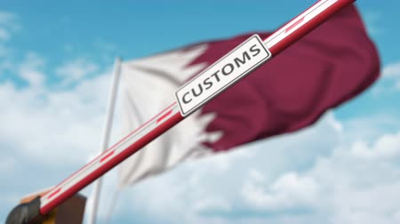 encerramento : Barrier gate with CUSTOMS sign being closed with flag of Qatar as a background. Qatari Border closure or protective tariffs