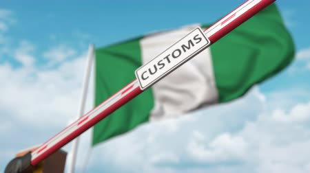 義務 : Closing boom barrier with CUSTOMS sign against the Nigerian flag. Restricted border crossing or protective tariffs in Nigeria