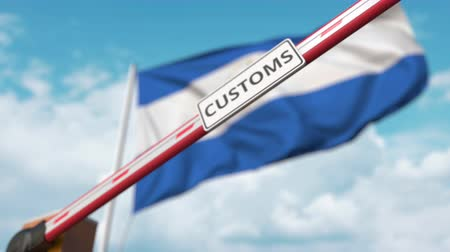 entry : Barrier gate with CUSTOMS sign being closed with flag of Nicaragua as a background. Nicaraguan restricted border crossing or protective tariffs