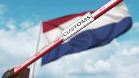 devoir : Closing boom barrier with CUSTOMS sign against the Dutch flag. Restricted border crossing or protective tariffs in Netherlands