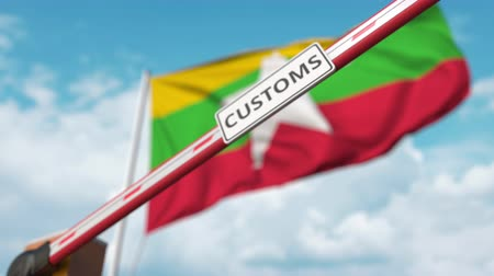 mianmar : Closing boom barrier with CUSTOMS sign against the Myanma flag. Restricted border crossing or protective tariffs in Myanmar