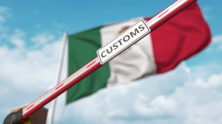 restringido : Closing boom barrier with CUSTOMS sign against the Mexican flag. Restricted border crossing or protective tariffs in Mexico