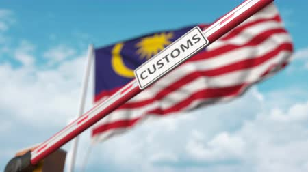 encerramento : Barrier gate with CUSTOMS sign being closed with flag of Malaysia as a background. Malaysian restricted border crossing or protective tariffs