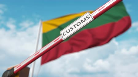 border crossing : Closing boom barrier with CUSTOMS sign against the Lithuanian flag. Restricted border crossing or protective tariffs in Lithuania
