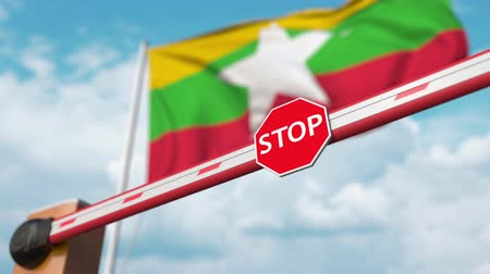 охрана : Opening boom barrier with stop sign against the Myanma flag. Free border crossing or lifting a ban in Myanmar
