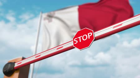 invite : Opening boom barrier with stop sign against the Maltese flag. Free border crossing or lifting a ban in Malta