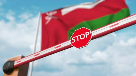 invite : Opening boom barrier with stop sign against the Omani flag. Free entry or lifting a ban in Oman Stock Footage