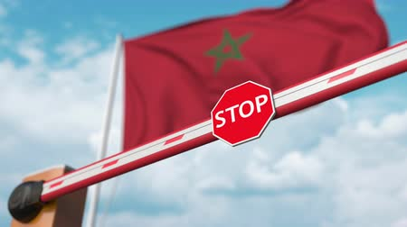 enable : Opening boom barrier with stop sign against the Moroccan flag. Free border crossing or lifting a ban in Morocco