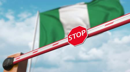 nigeria flag : Opening boom barrier with stop sign against the Nigerian flag. Free border crossing or lifting a ban in Nigeria