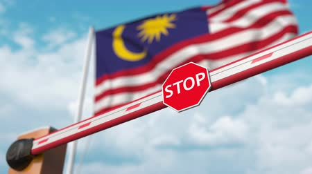 convidar : Barrier gate being opened with flag of Malaysia as a background. Malaysian Free border crossing or lifting a ban