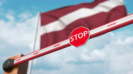 enable : Barrier gate being opened with flag of Latvia as a background. Latvian Free border crossing or lifting a ban