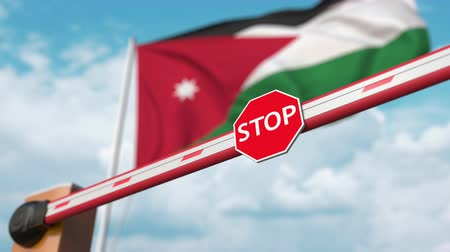 border crossing : Barrier gate being opened with flag of Jordan as a background. Jordanian Free border crossing or lifting a ban Stock Footage
