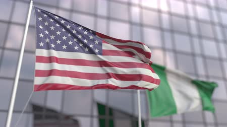 ассоциация : Waving flags of the USA and Nigeria in front of a modern skyscraper
