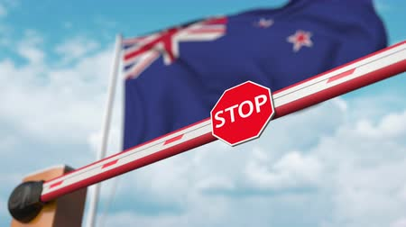 nowa zelandia : Opening boom barrier with stop sign against the flag. Free border crossing or lifting a ban in New Zealand