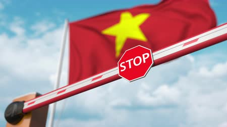 enable : Opening boom barrier with stop sign against the Vietnamese flag. Free entry or lifting a ban in Vietnam