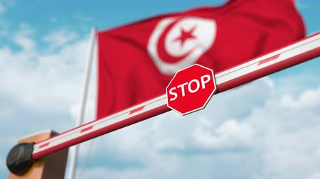 authorise : Opening boom barrier with stop sign against the Tunisian flag. Free border crossing or lifting a ban in Tunisia Stock Footage