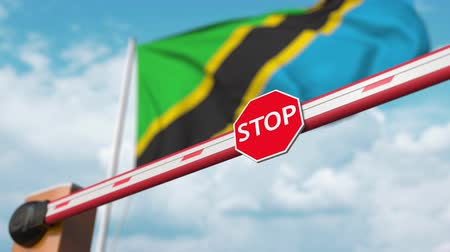 entry : Opening boom barrier with stop sign against the Tanzanian flag. Free border crossing or lifting a ban in Tanzania
