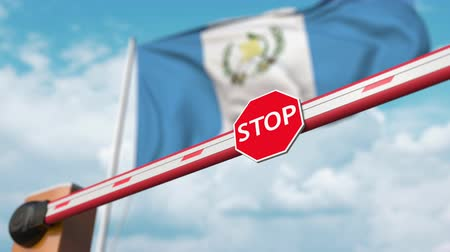 abriu : Barrier gate being opened with flag of Guatemala as a background. Guatemalan Free entry or lifting a ban Stock Footage