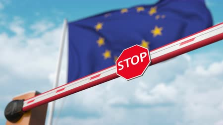 abriu : Barrier gate being opened with flag of the EU as a background. European Free entry or lifting a ban Stock Footage