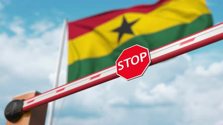 authorise : Opening boom barrier with stop sign against the Ghanaian flag. Free entry or lifting a ban in Ghana Stock Footage