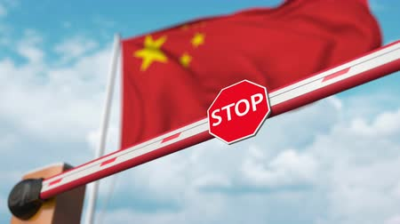 gümrük : Opening boom barrier with stop sign against the Chinese flag. Free entry or lifting a ban in China Stok Video