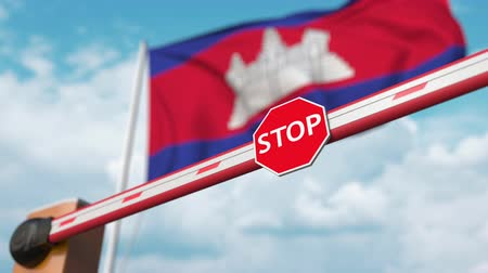 enable : Opening boom barrier with stop sign against the Cambodian flag. Free entry or lifting a ban in Cambodia Stock Footage