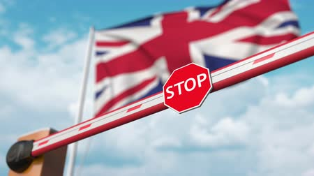 immigratie : Barrier gate being opened with flag of the United Kingdom as a background. British free entry or lifting a ban Stockvideo